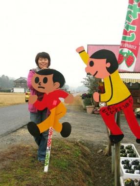 """インドへ行く前の永田純子さんとおそらくインド初上陸となるとび太くん(栗東市東坂にある「びにーる美術館」前)。右に設置されたものはコンテストで生まれた「""""世界に""""とびだそう坊や」"""