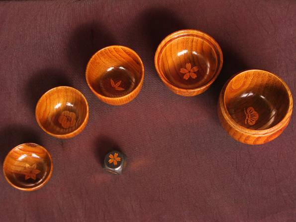 だるまの上下とを合わせ、5つの盃になります。それぞれの盃の底に、松竹梅と桜、麻柄の印が押されています。さいころの5つの目にもそれぞれに同じ絵柄があり、残りのひとつの目は音符になっています。