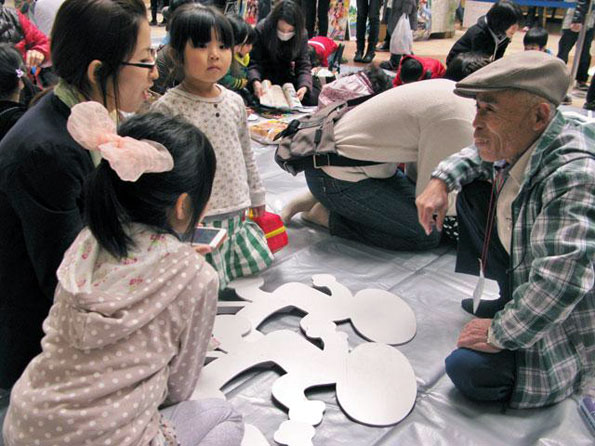 丁寧に飛び出し坊やの作り方を指導する久田泰平さん。自分の手で飛び出し坊やを作った子達は決して「飛び出し」なんかしないことでしょう